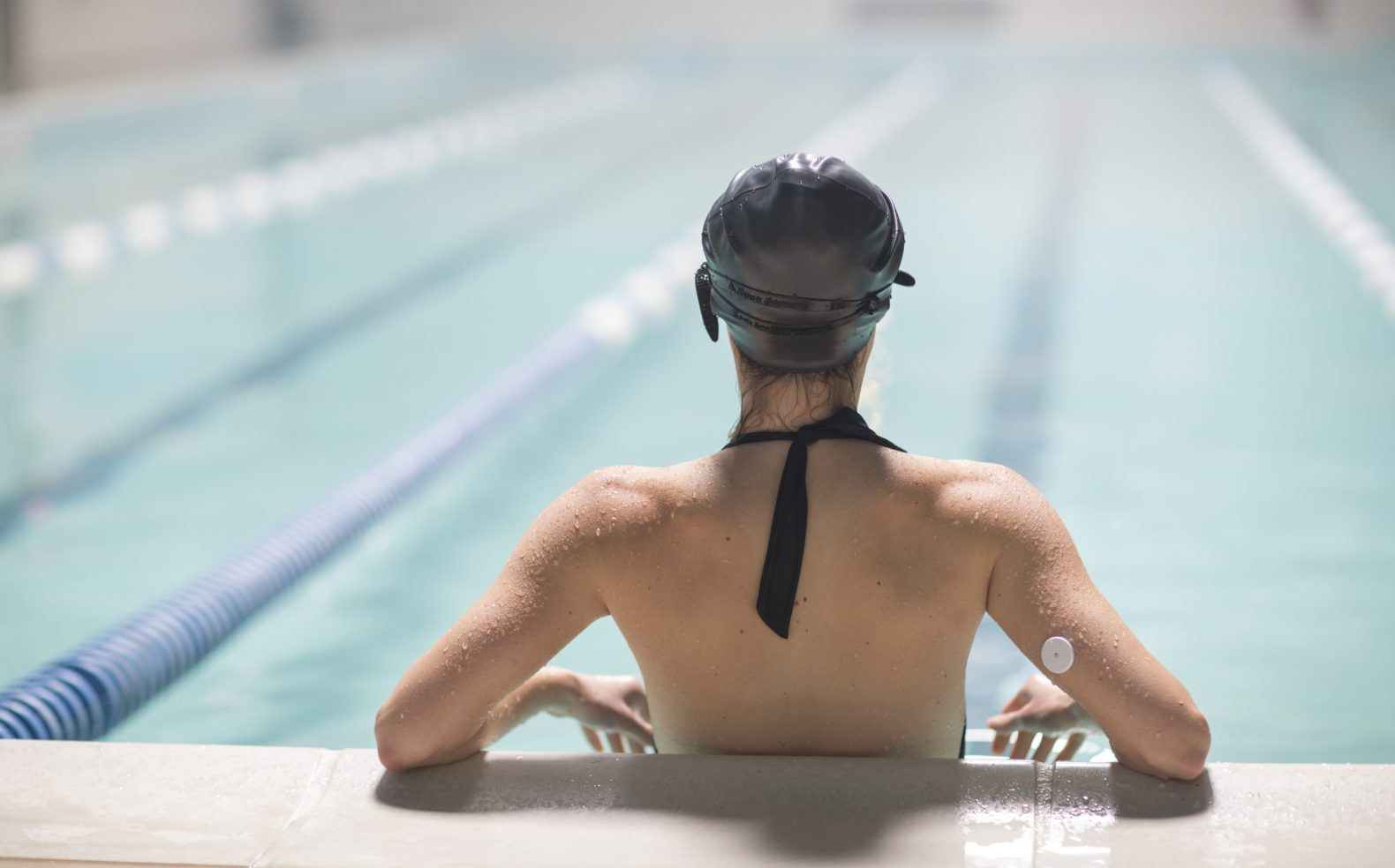 A swimmer in a pool with elbows propped up on the concrete edge facing swimming lanes and wearing a medical patch on her arm.