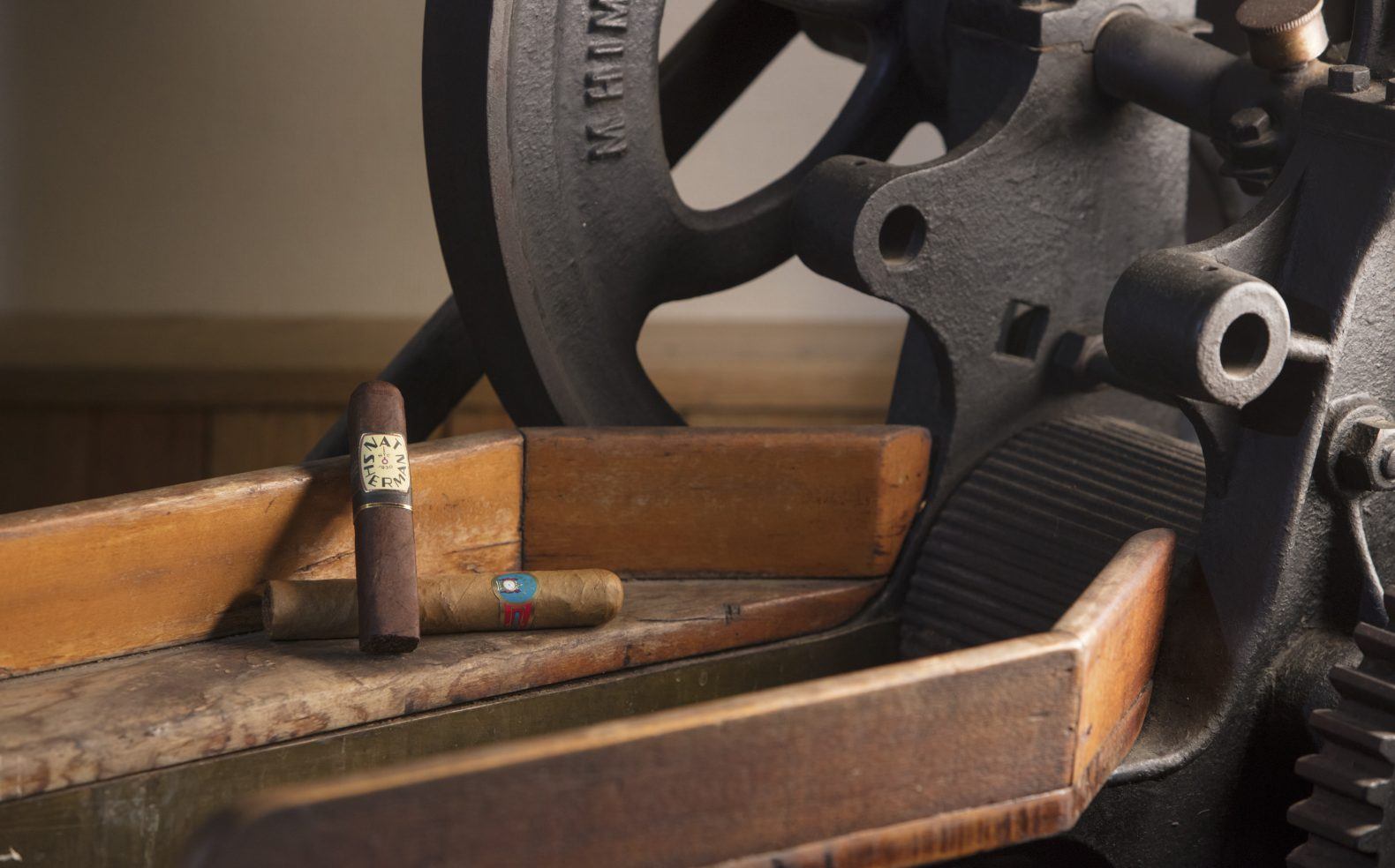 Two cigars being propped up for display on the wooden side of an antique cigar press.