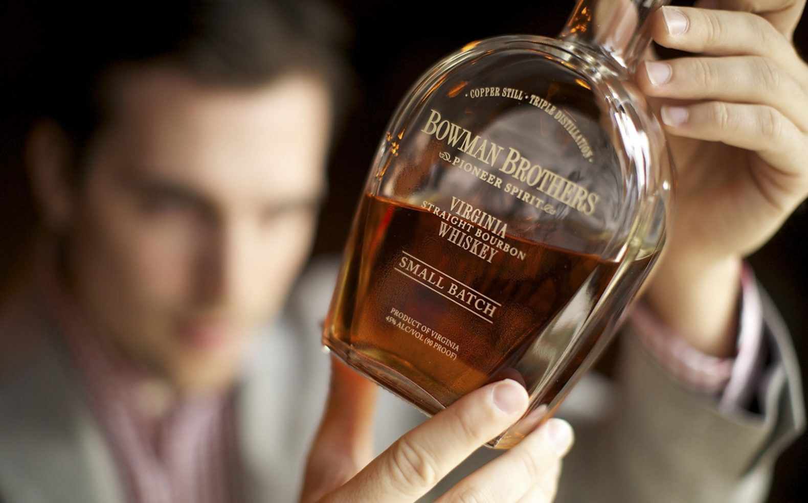 A bottle of Virginia whiskey in the foreground being held and inspected by a man out of focus in the background.
