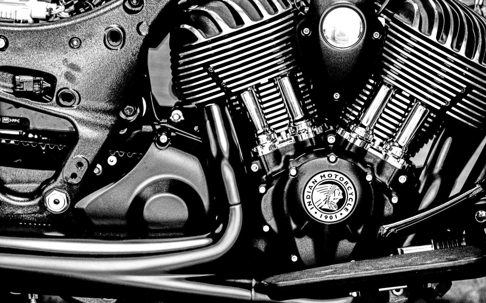 Black and white close-up photograph of a motorcycle engine that is powder coated in flat black paint.