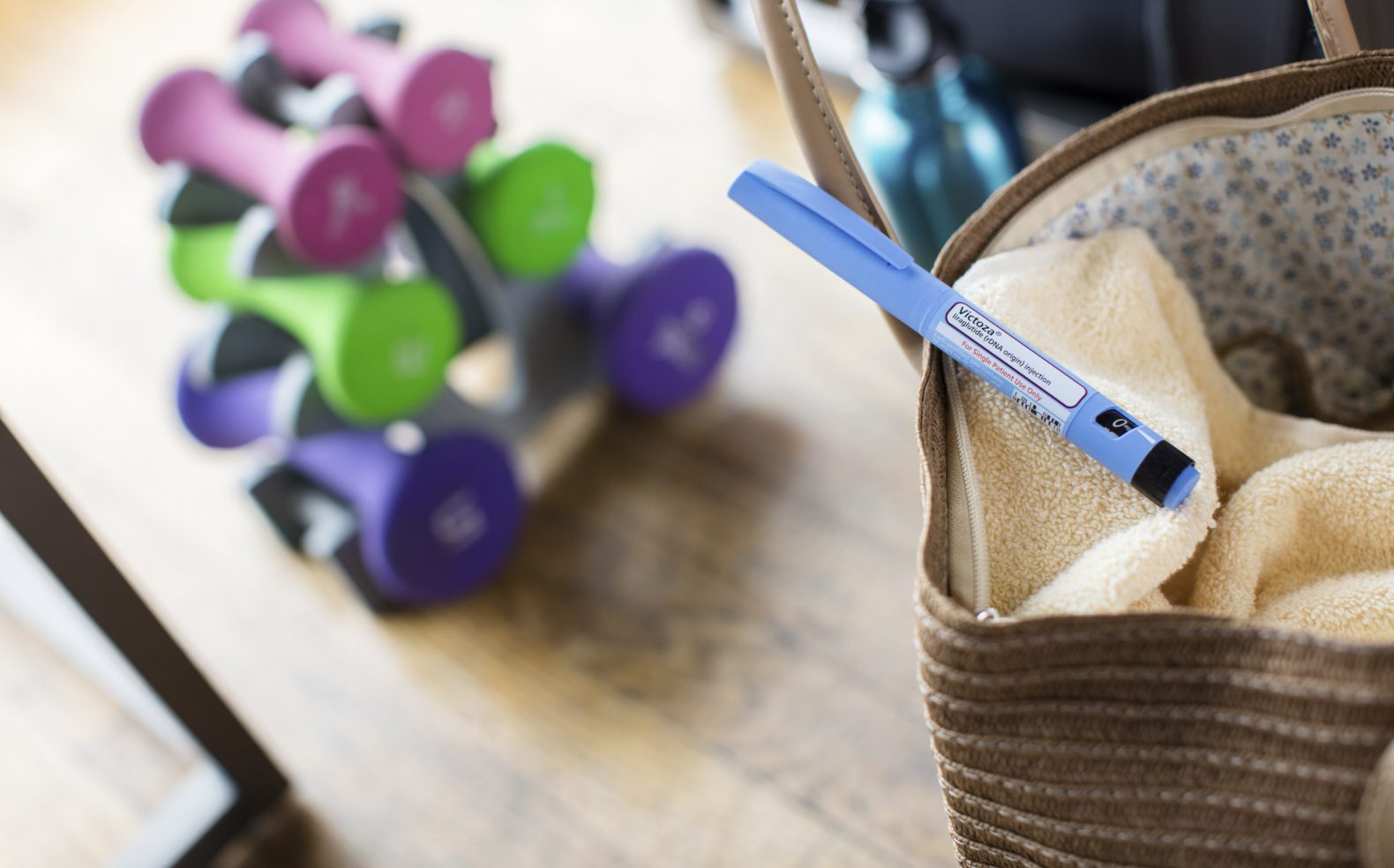 A medical diabetes pen laying on a towel in a tote bag surrounded by weights and other workout equipment.