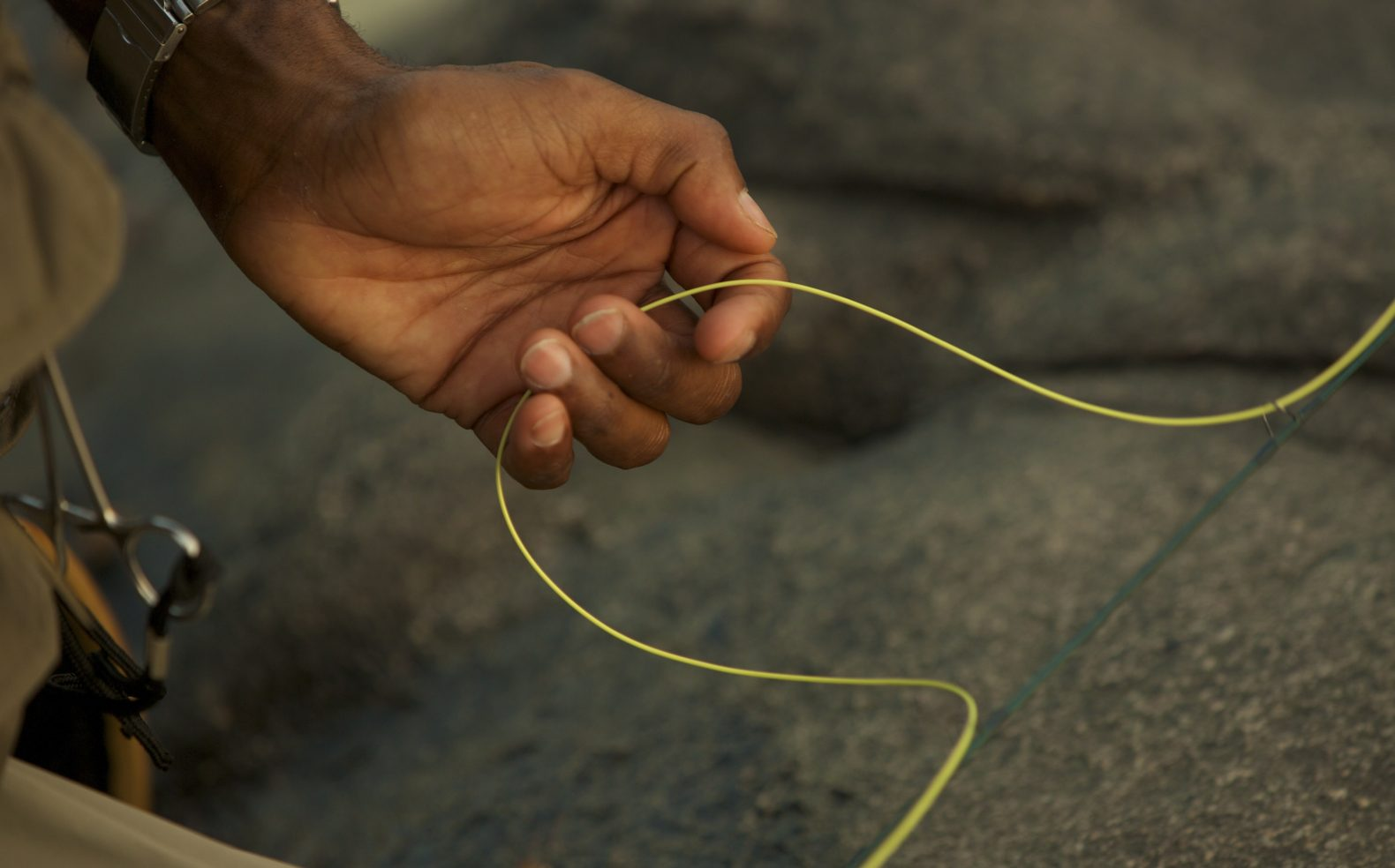 Professional photograph of a fisherman's hand in front of rocks gently holding a yellow fishing line