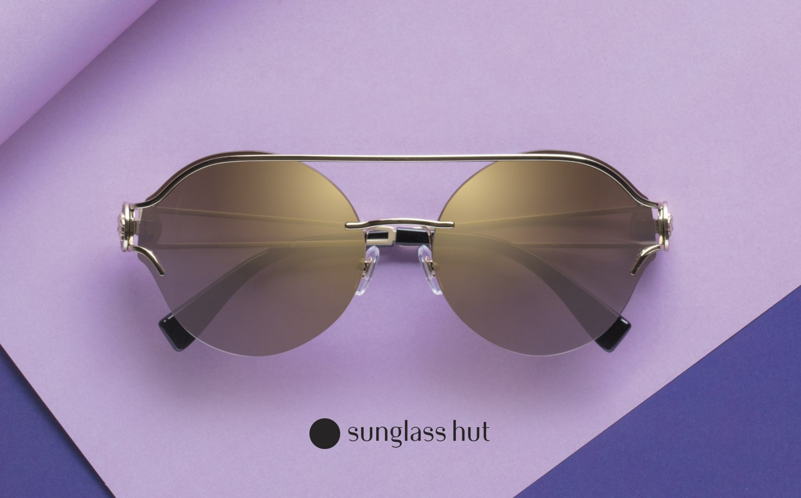 Professional product photograph of a pair of chic sunglasses on a background of purple colored paper with Sunglass Hut logo.