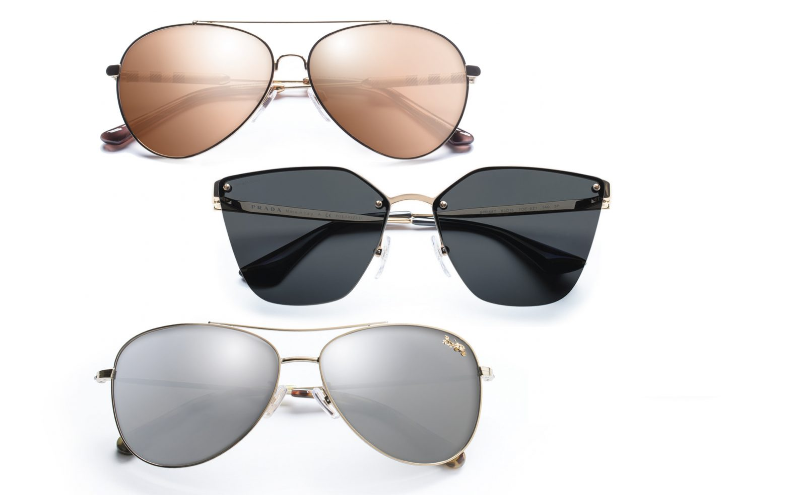 Professional product photograph of three pairs of chic designer sunglasses on a white background
