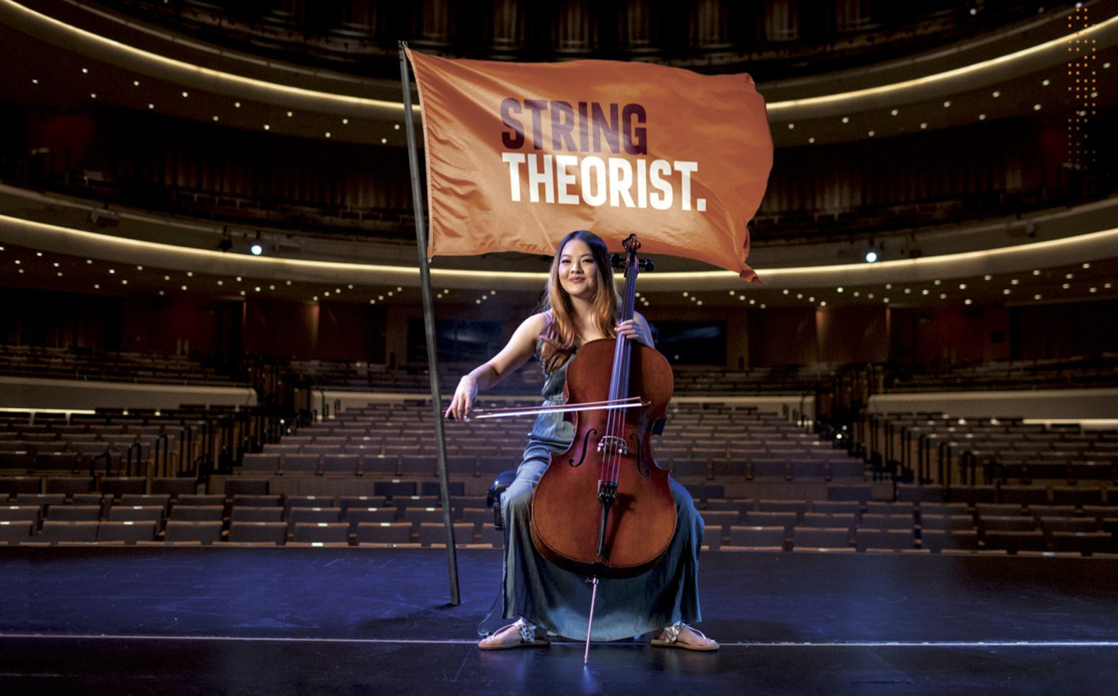 """Professional university advertising photograph of a musician sitting proudly on a stage in front of a flag with text """"String Theorist"""""""