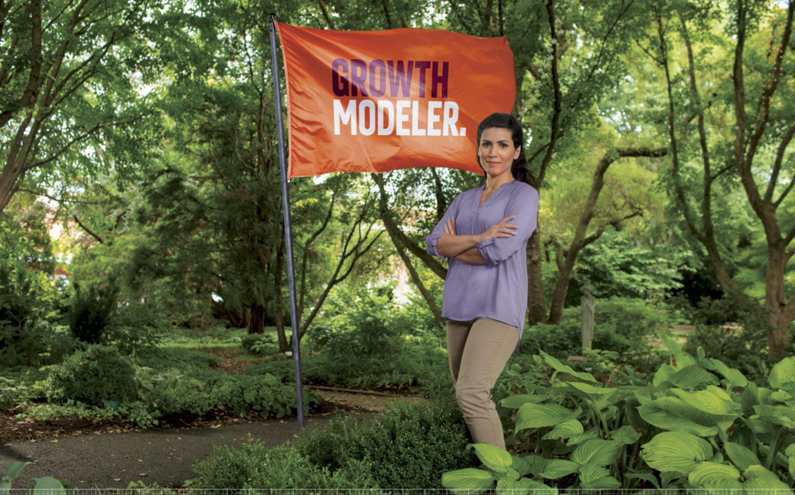 "Professional university advertising photograph of a woman standing in the woods in front of a flag with text ""Growth Modeler"""