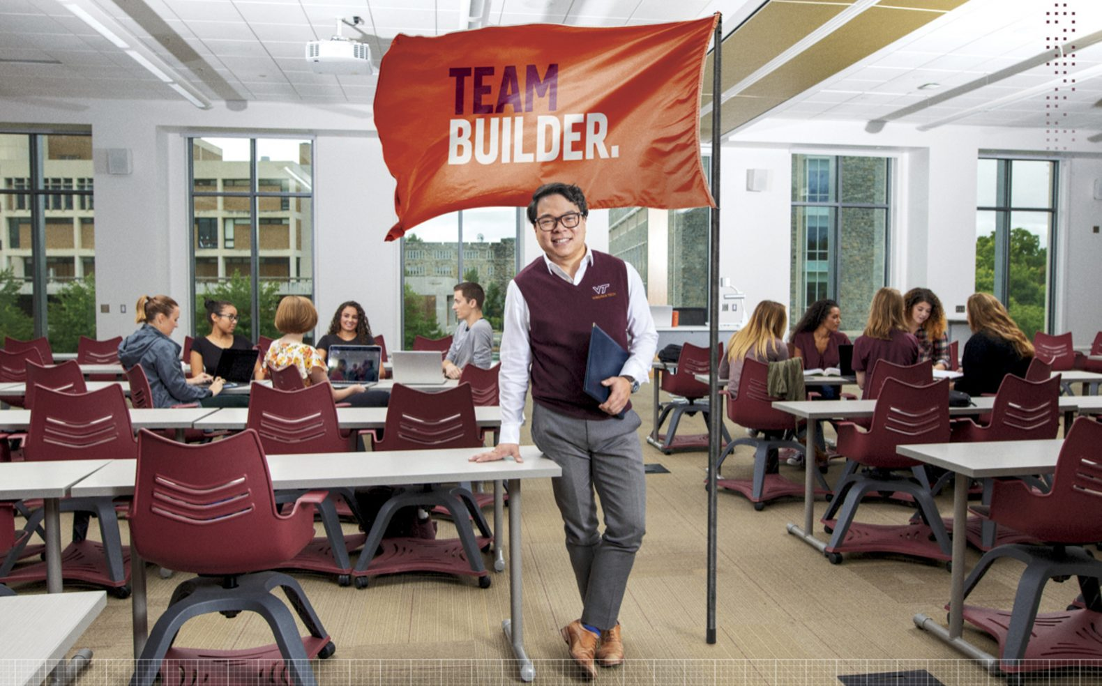 "Professional university advertising photograph of a man standing proudly in a classroom in front of a flag with text ""Team Builder"""