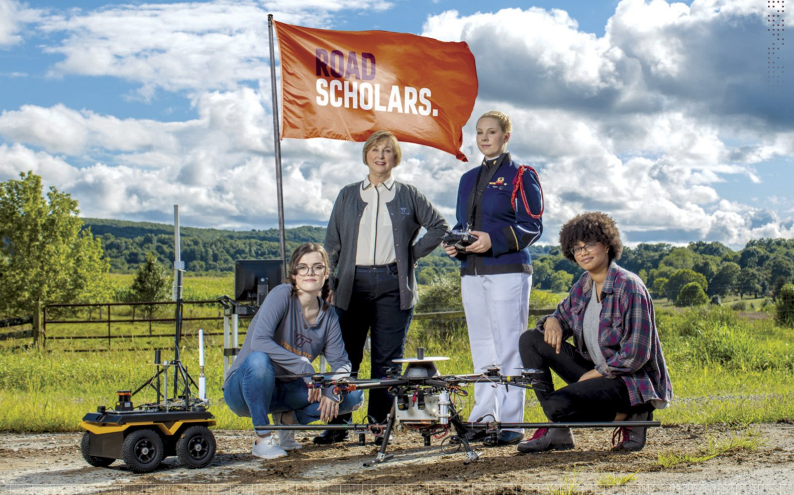 "Professional university advertising photograph of four women with technical machines in front of a flag with text ""Road Scholars"""