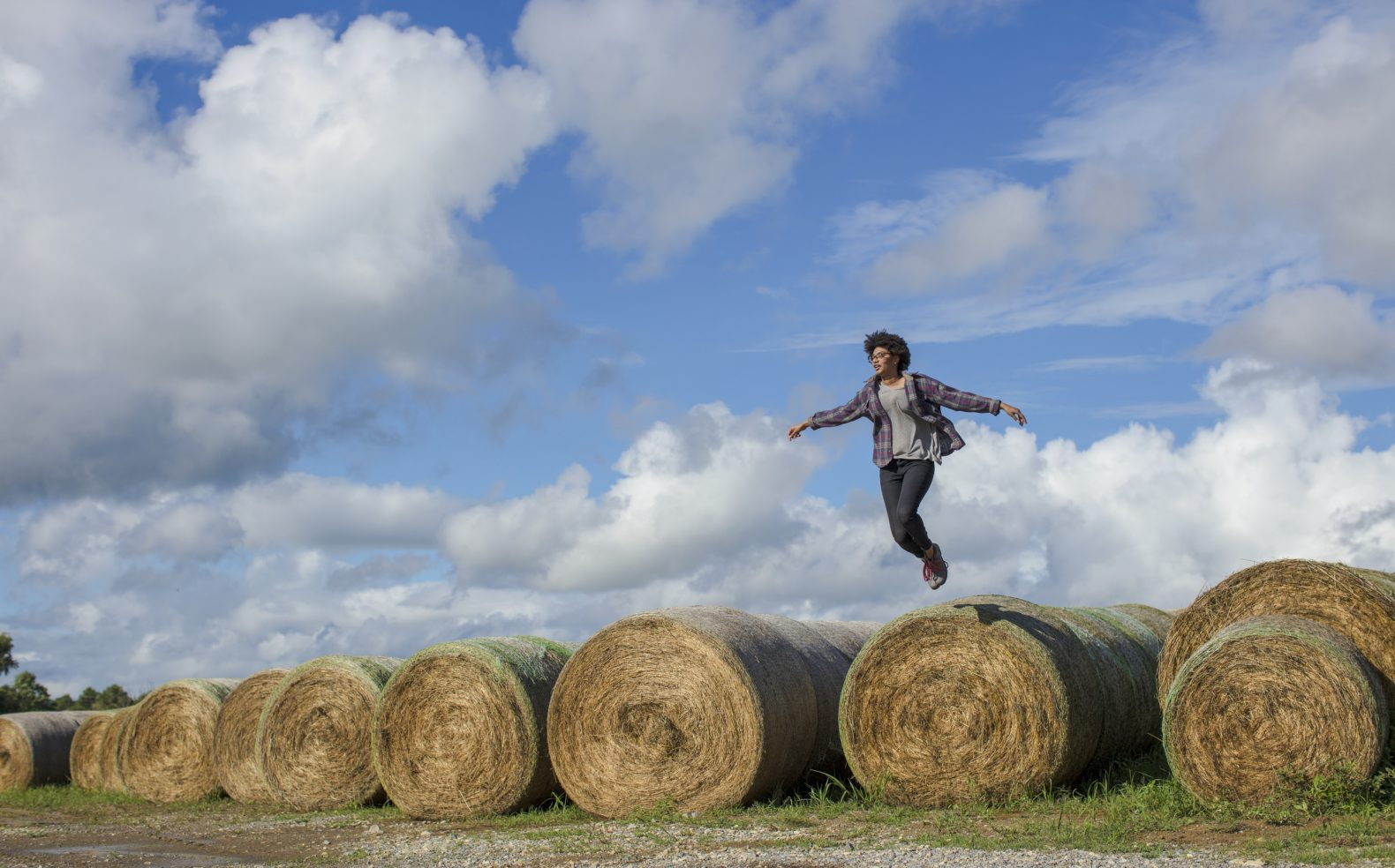 A young woman wearing jeans and a flannel is airborne as she jumps off a row of hay barrels under a blue sky.