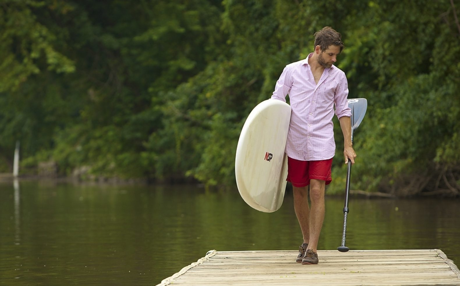 A man in a collard shirt and board shorts walks on a dock looking at the ore in his left hand and holding a paddle board in his other arm.