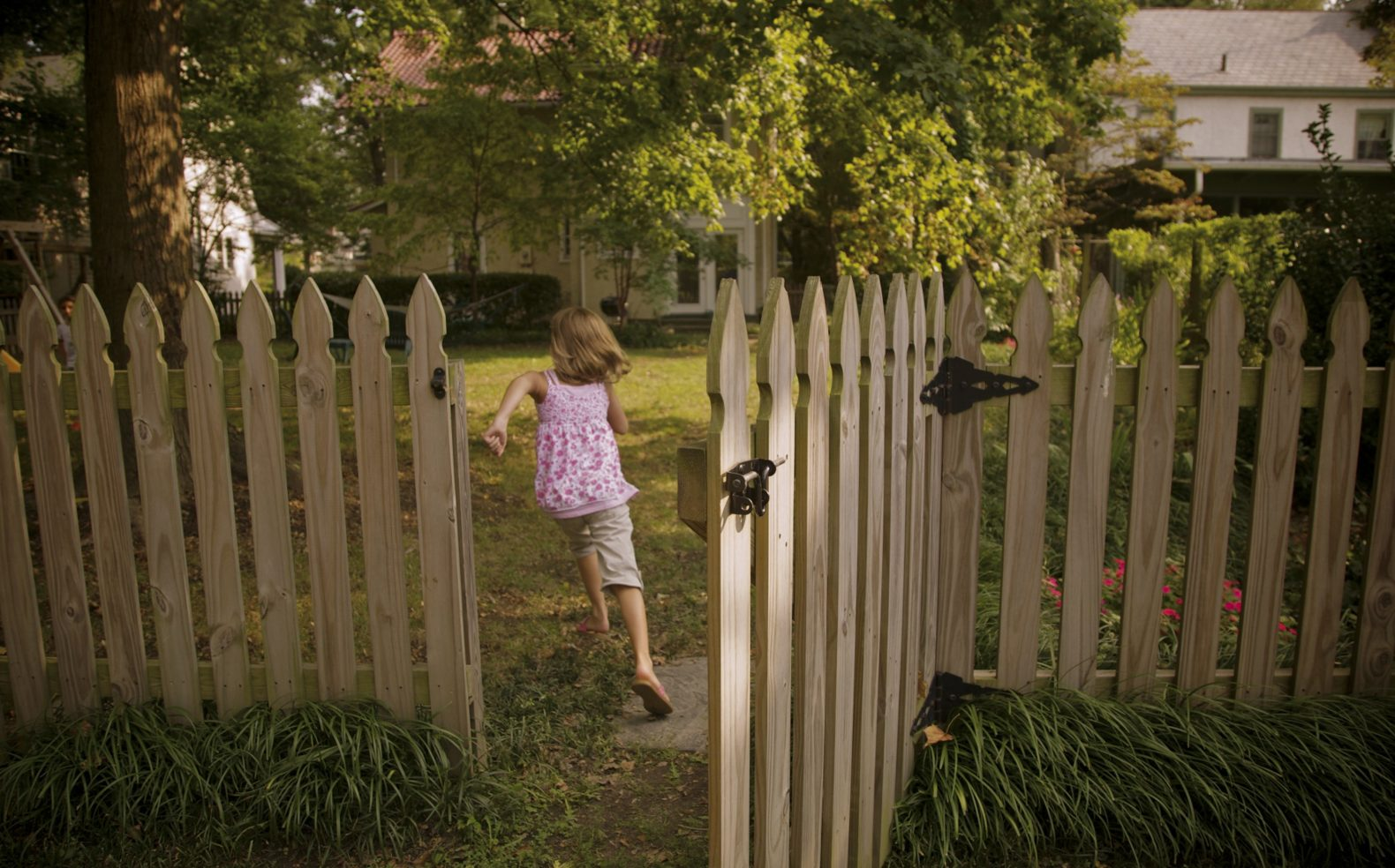 A young girl in spring apparel running through an open fence door into a backyard with greenery and sunlight.