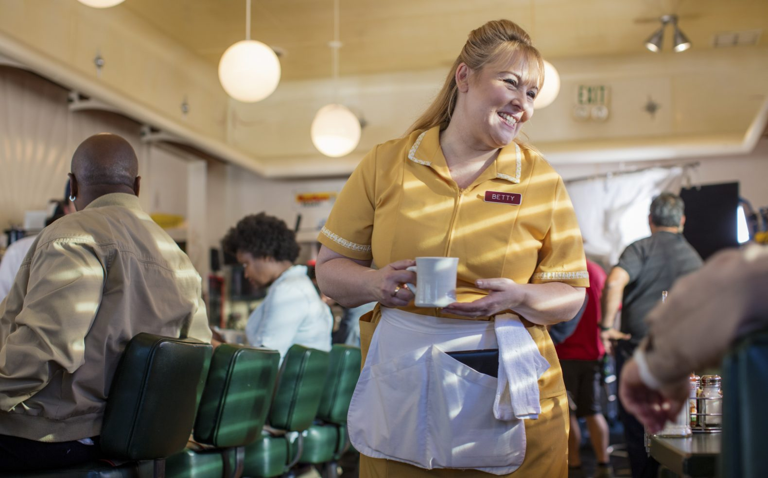 A waitress in a yellow diner uniform walking through the diner holding a cup of coffee and smiling at a customer.