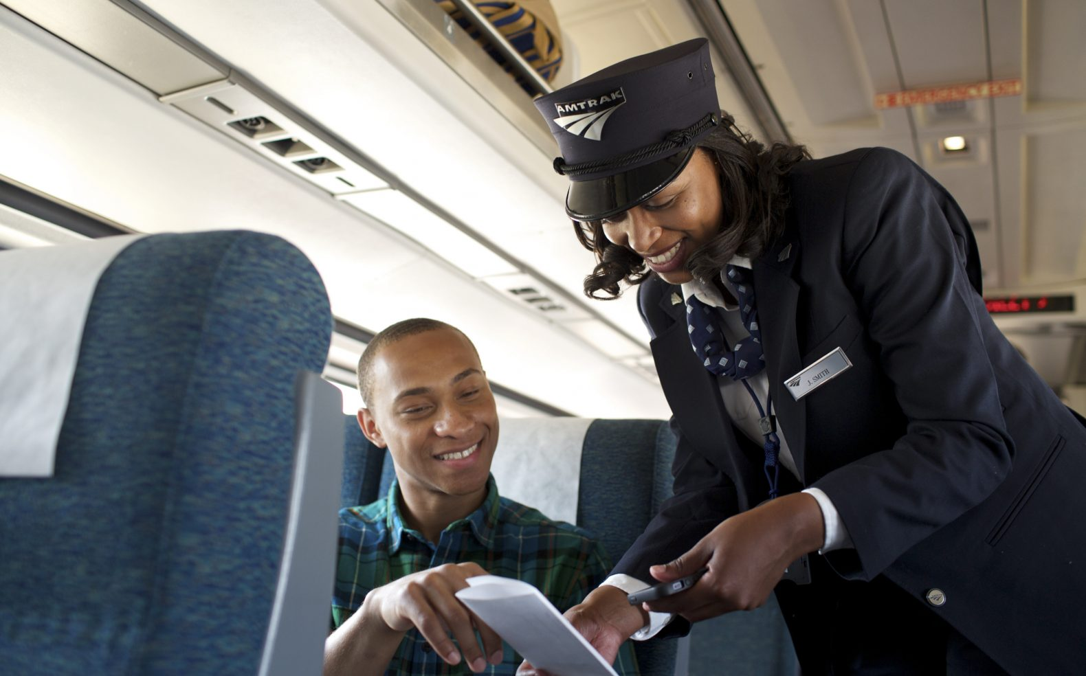 An Amtrak train employee and passenger smile as the passenger holds his ticket as the employee examines it.