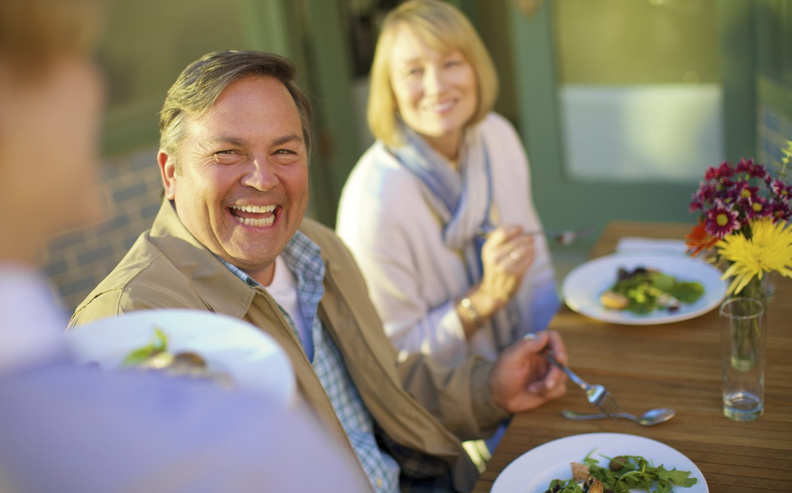 Professional photograph of a couple smiling while enjoying a summer salad