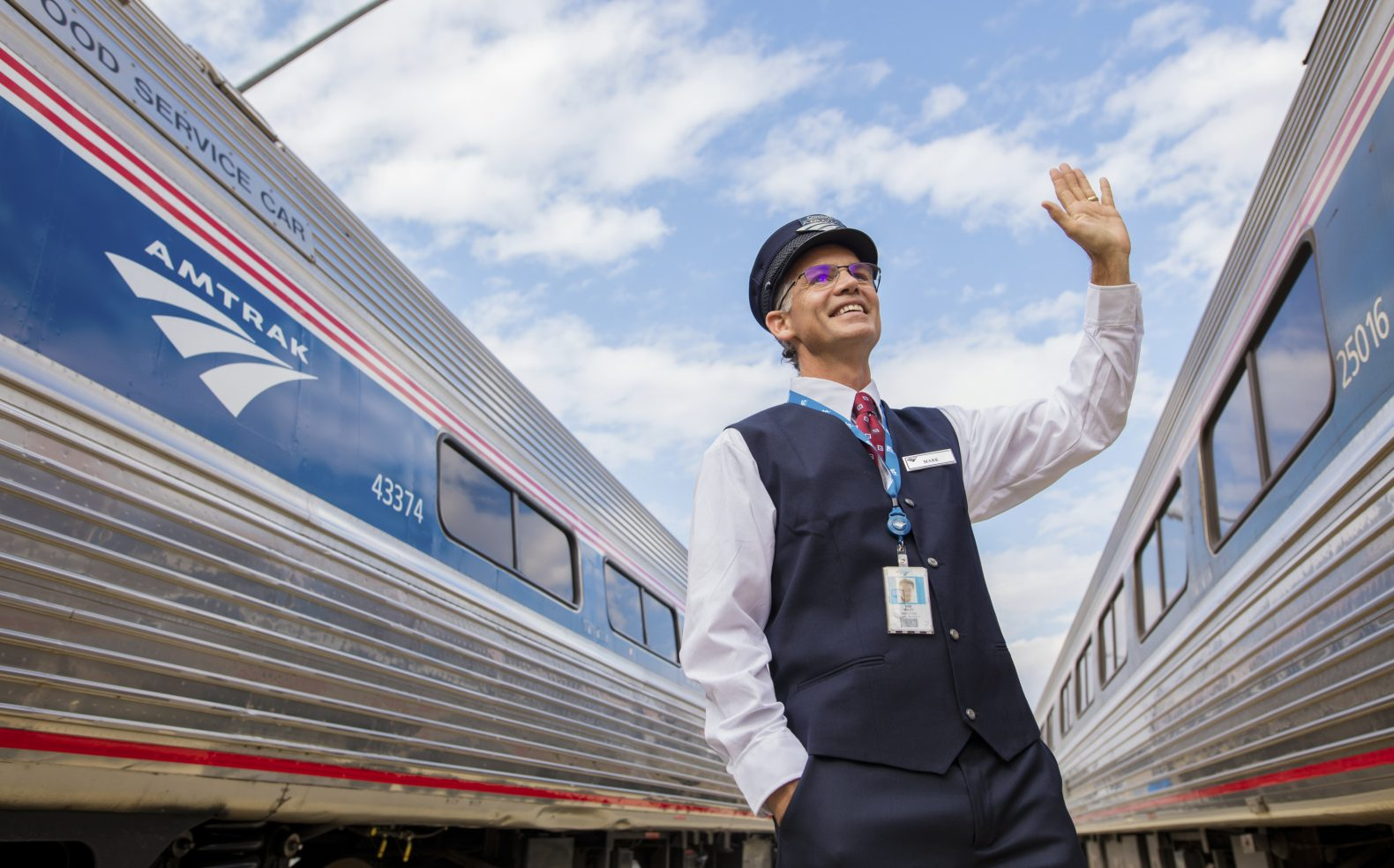 Professional photograph of an Amtrak train employee on a platform between two trains waving as a train passes by.
