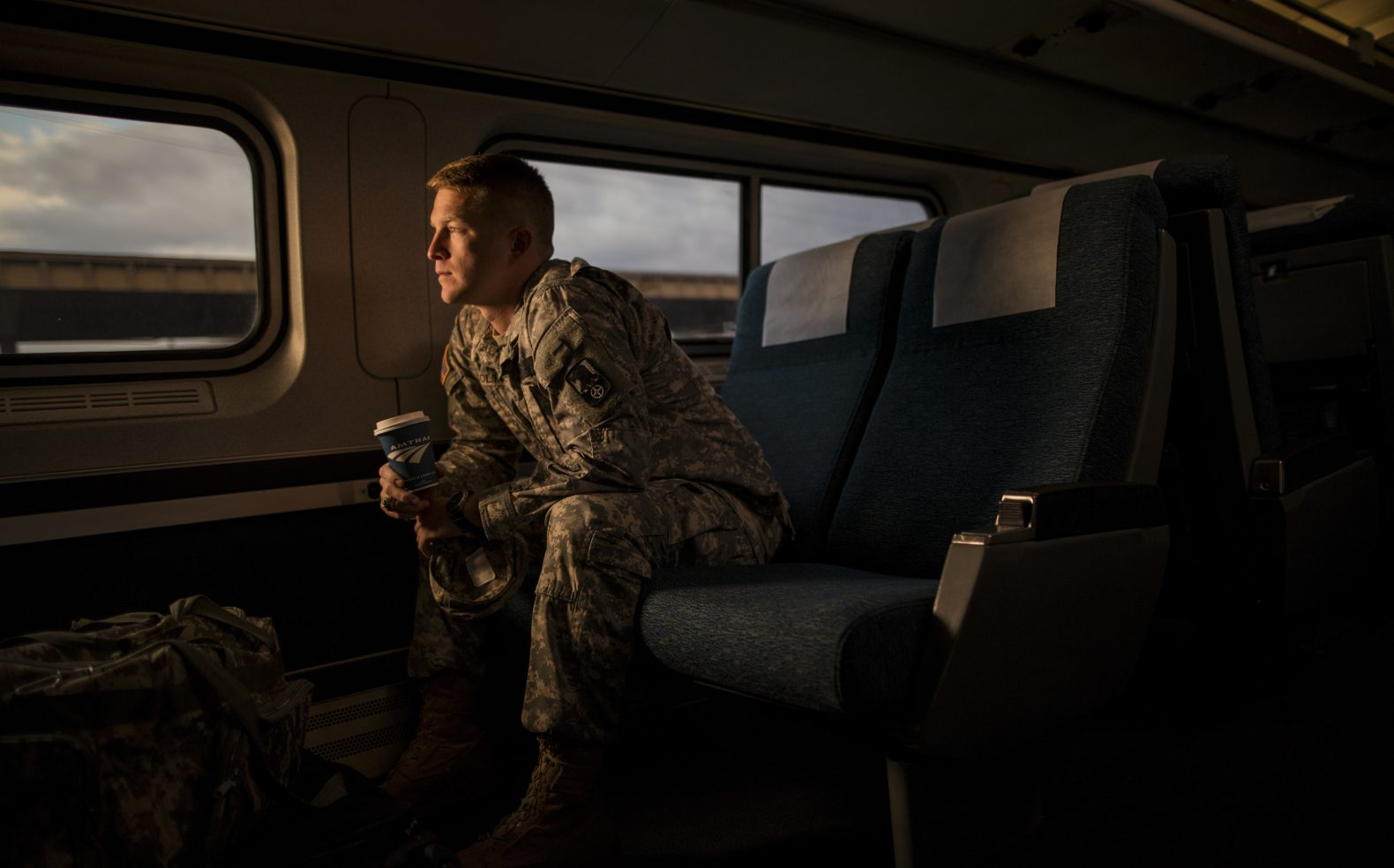 Professional photograph of USA Military soldier in uniform enjoying a cup of coffee while riding the Amtrak train in early morning.