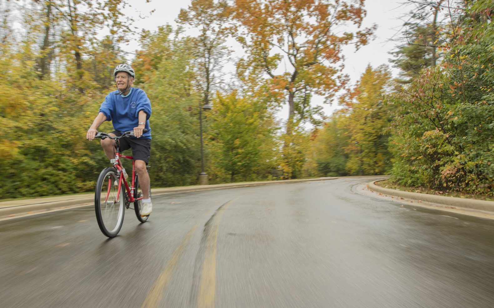 Professional photograph of an older man enjoying a bike ride on a road by trees on a crisp fall day.
