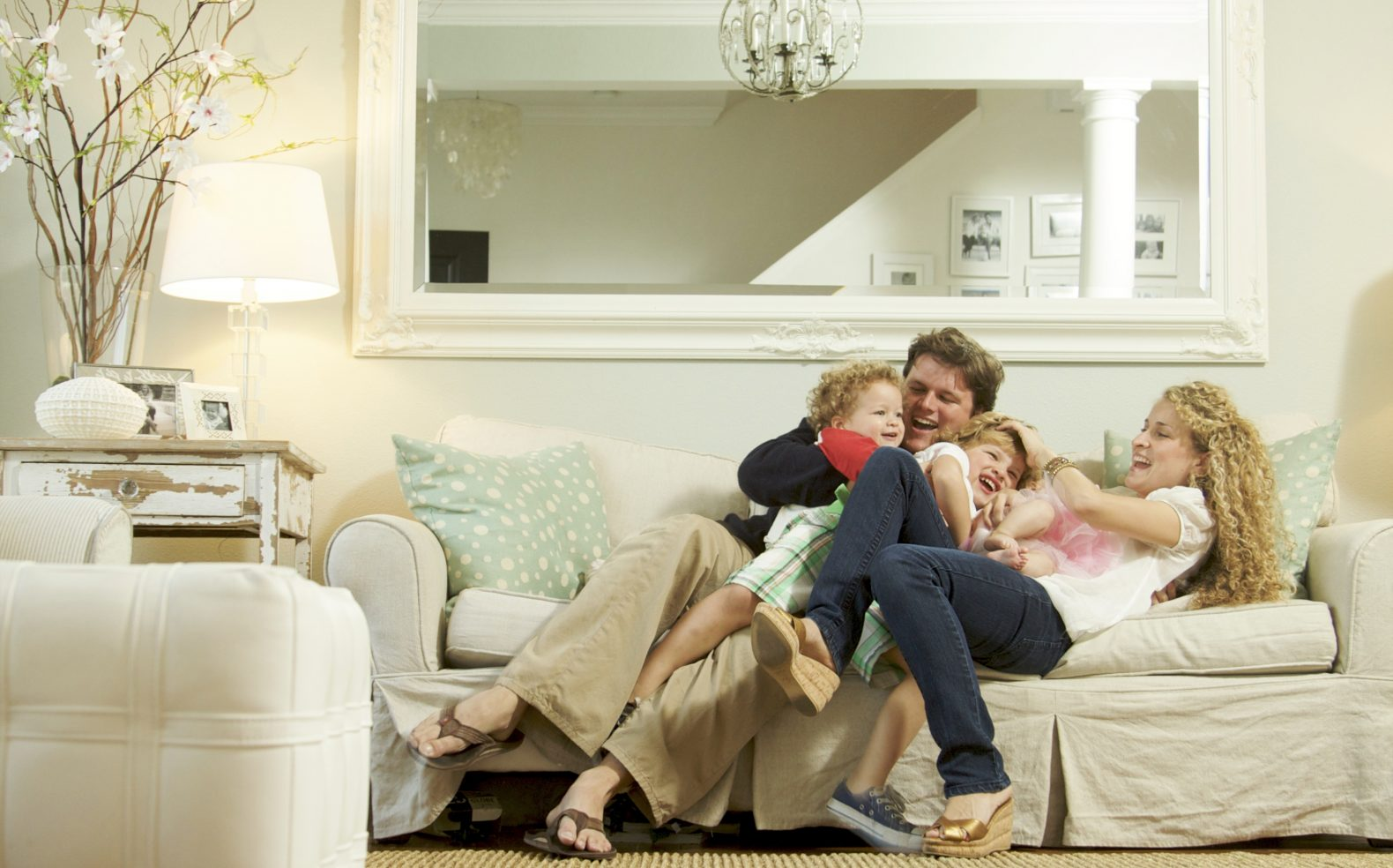 Professional photograph of young family snuggling and laughing on a living room couch