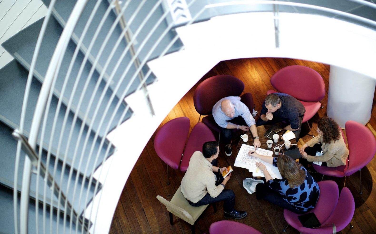 Overhead view from a curved staircase of five business professionals sitting around a small table with coffee and documents.