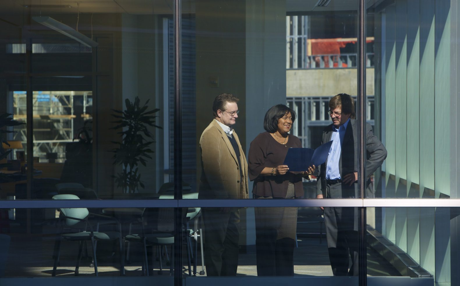 Professional photograph of three established businesspeople standing and reviewing a document by an office window