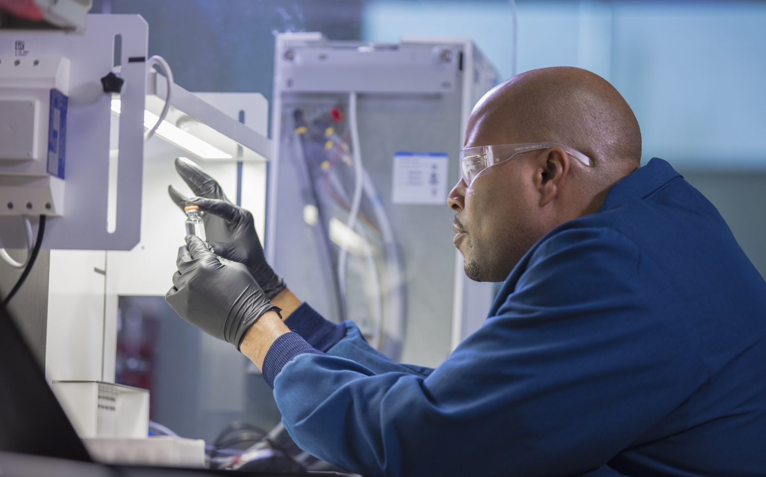 Profile view of a pharmaceutical employee in lab glasses and black gloves sitting and examining a clear, liquid sample.