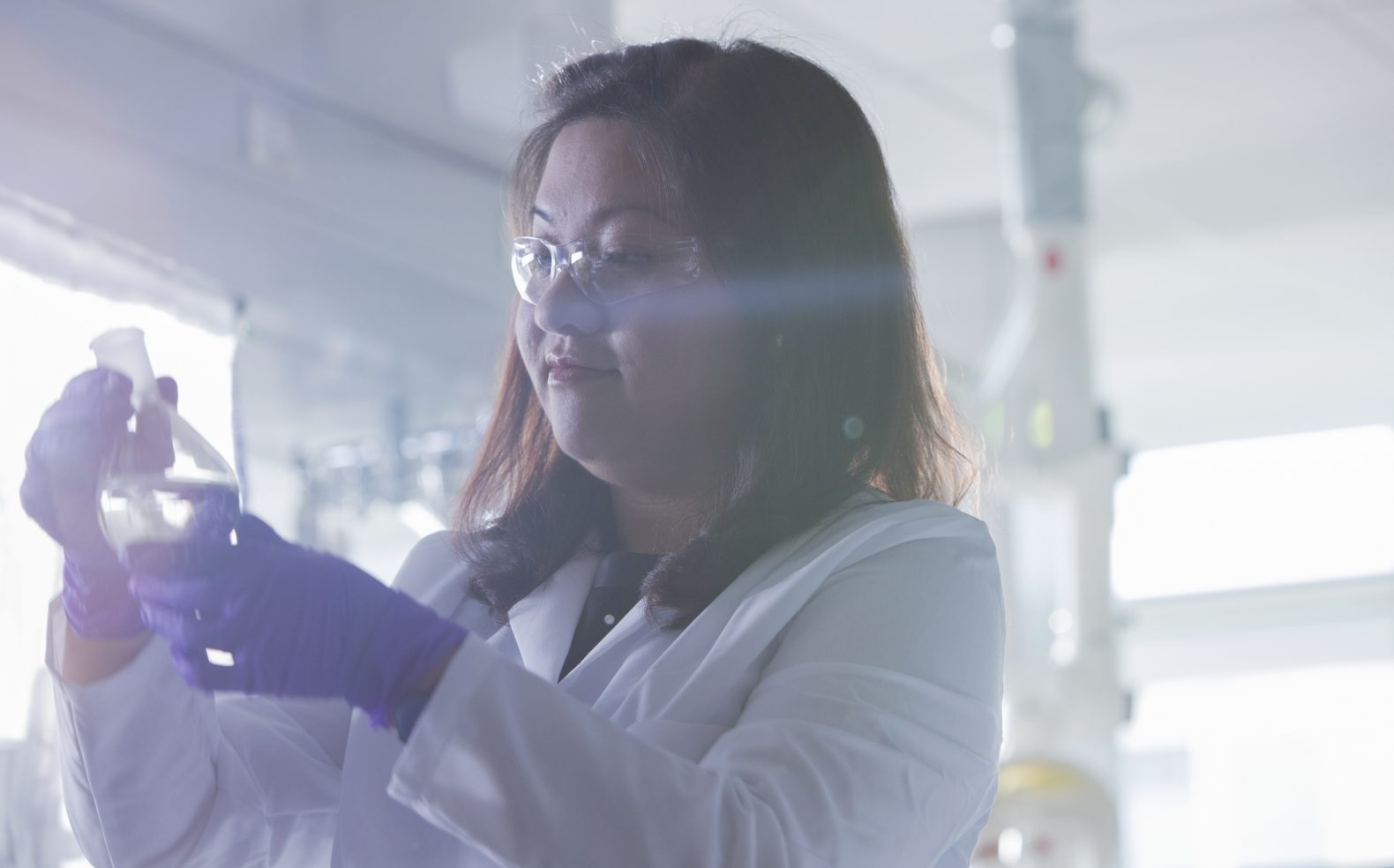 Professional photograph of a scientist examining a sample in a lab