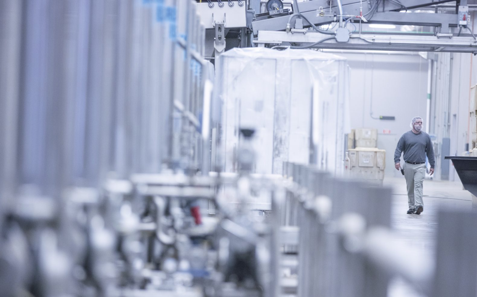 Professional photograph of a manufacturing employee walking through a facility with metal machinery
