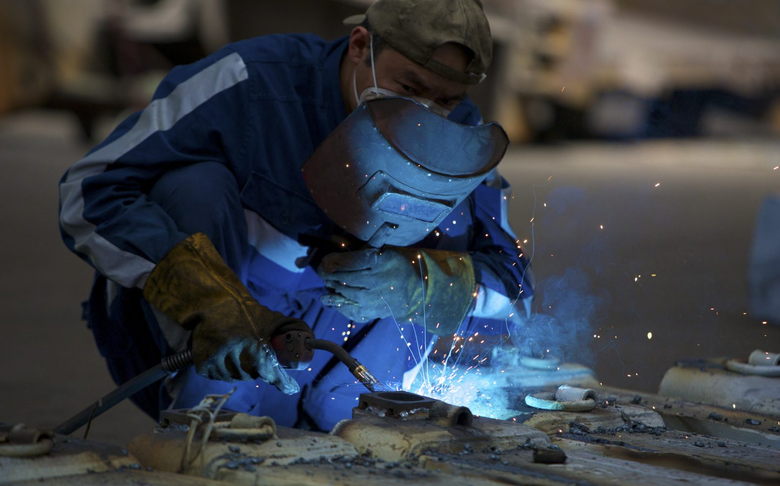 Professional photograph of a manufacturing employee welding in a facility with machinery in one hand and a face cover in the other hand