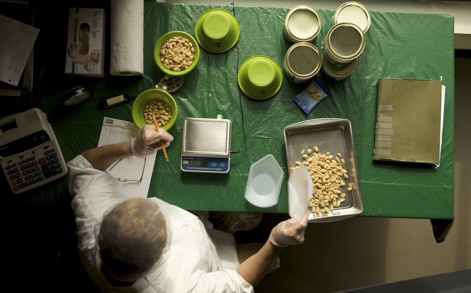 Professional photograph with overhead view of a manufacturing employee sorting and weighing peanuts on a table