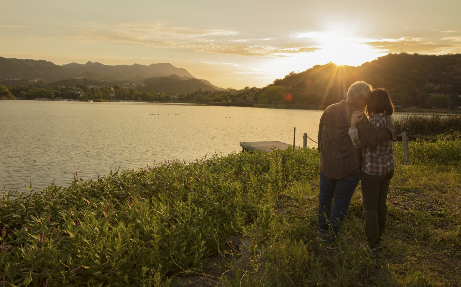 A middle-aged couple standing and embracing in grass next to a dock on a lake while the sun sets over the lake and mountains.