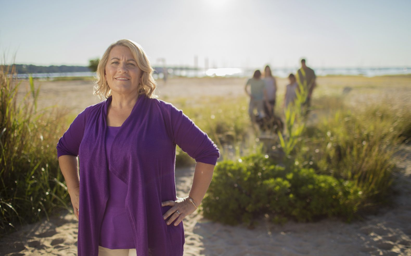 A middle-aged woman in a purple blouse stands on a beach with her hands on her hips, her family walks on sand in the background.