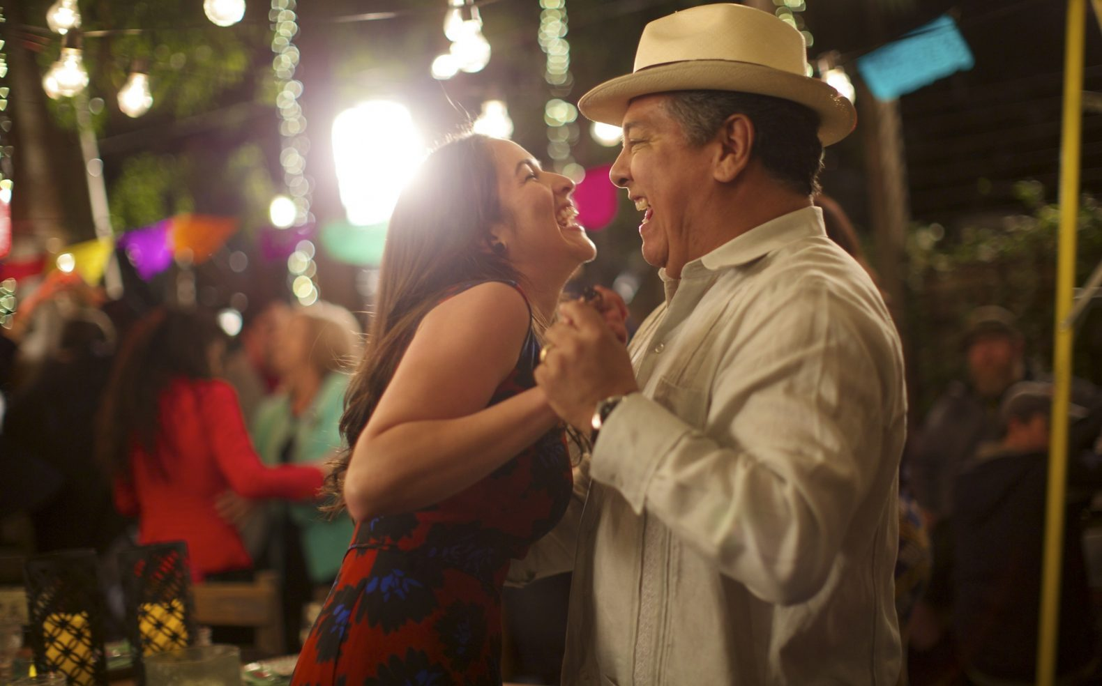 A father and adult daughter laughing and dancing at a festive party with string lights in the background.