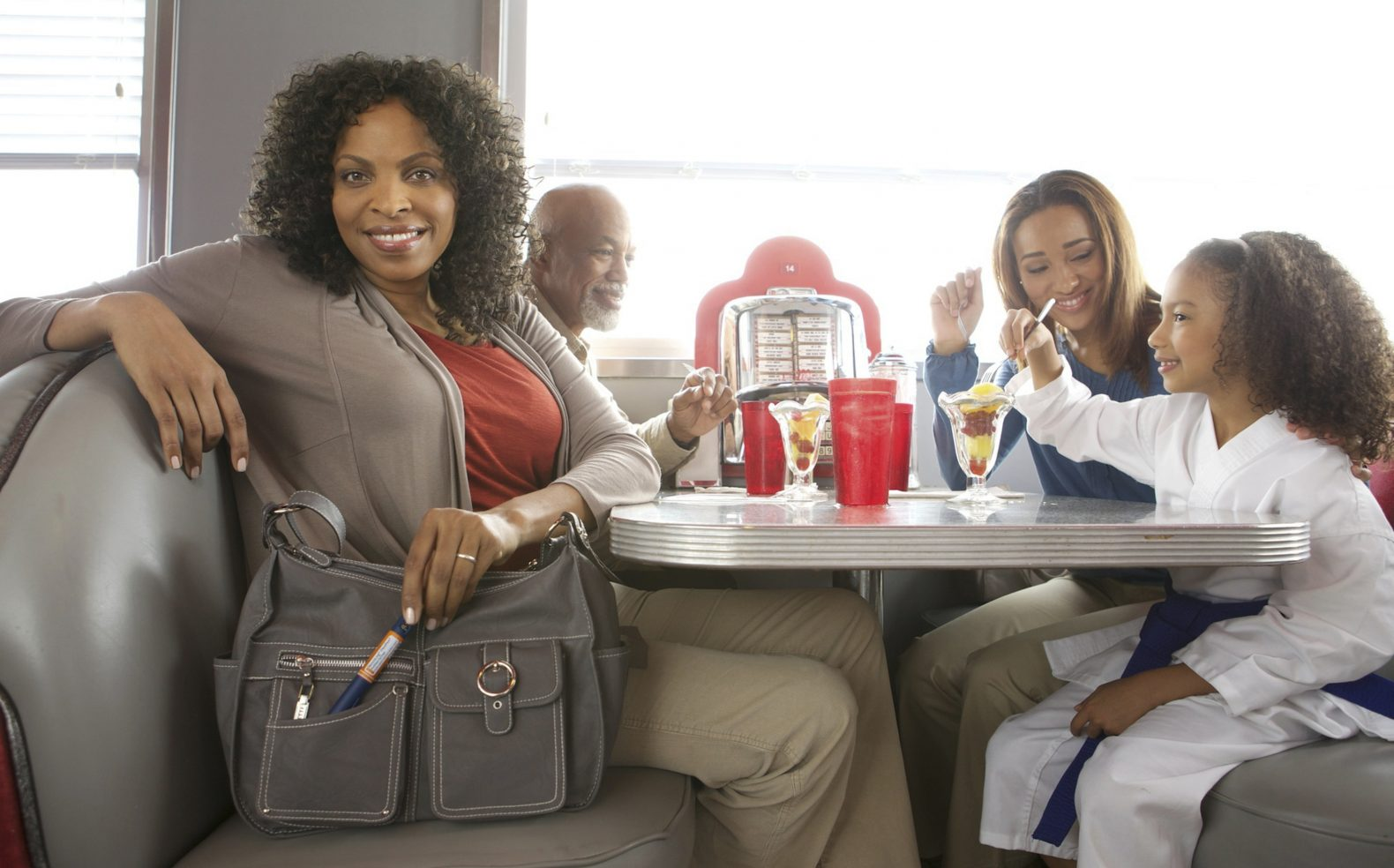A family sharing fresh fruit cups at a diner while the mom looks at the camera showing the medical pen in her purse.