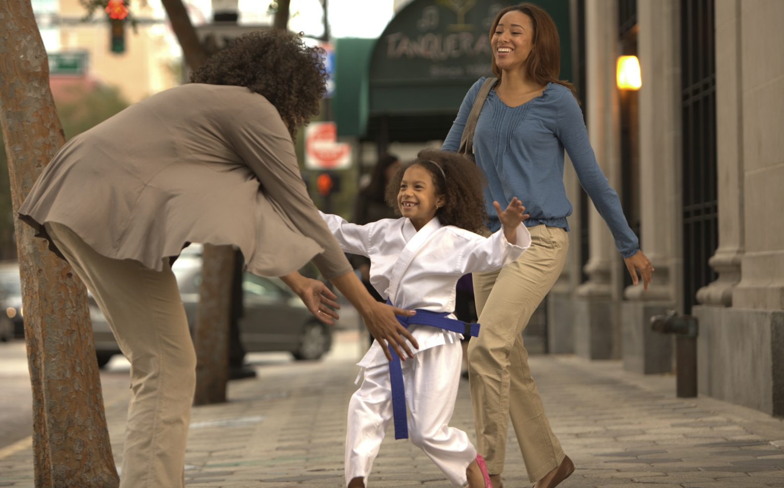 A young girl in a tikwondo robe running to embrace her grandmother outside of a taekwondo class while her mom smiles nearby.