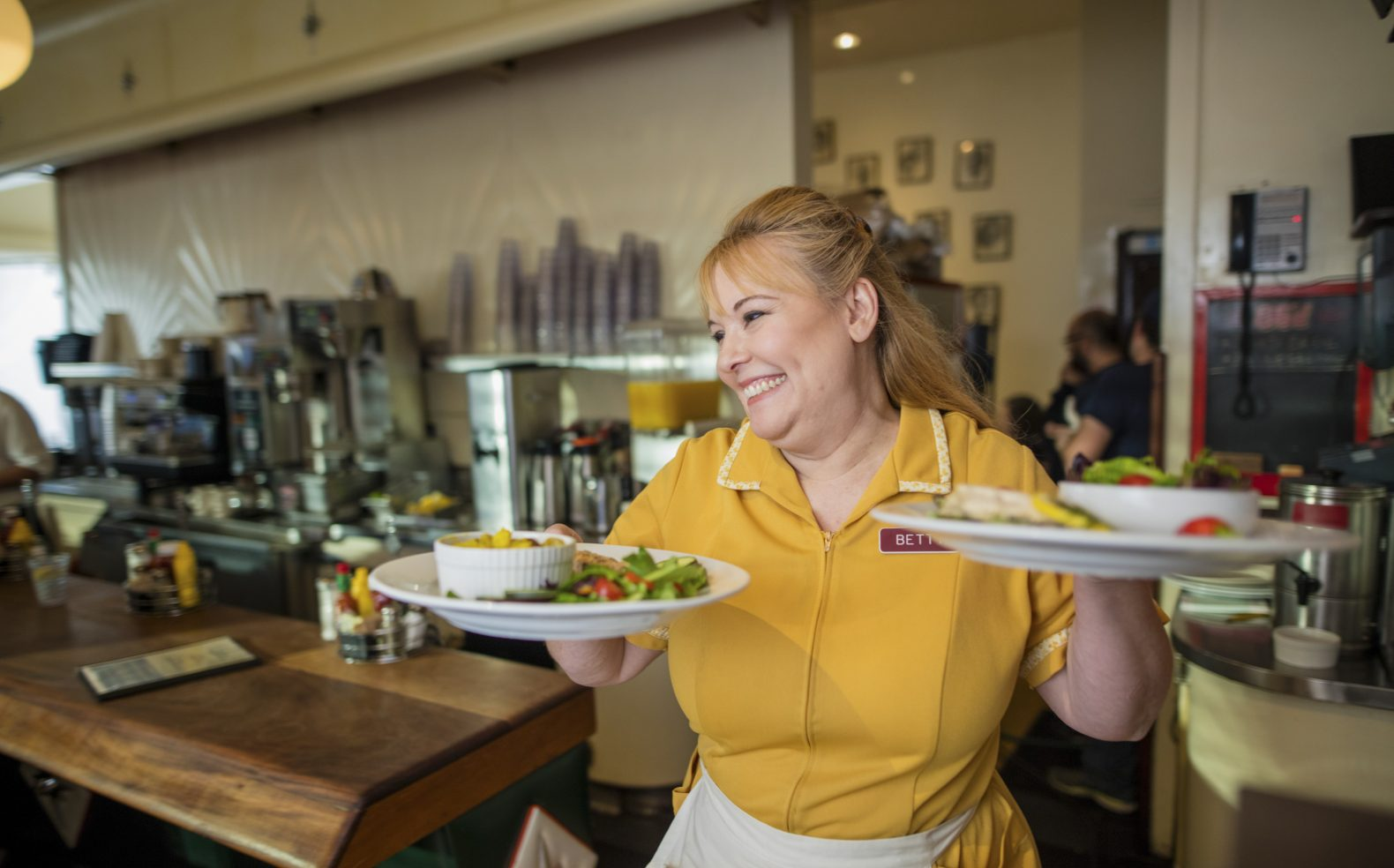 Professional production photograph of a waitress smiling while serving meals at a diner