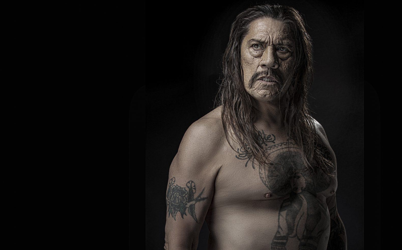 Professional production portrait of a strong middle-aged man with tatoos and no shirt and shoulder length dark straight hair.