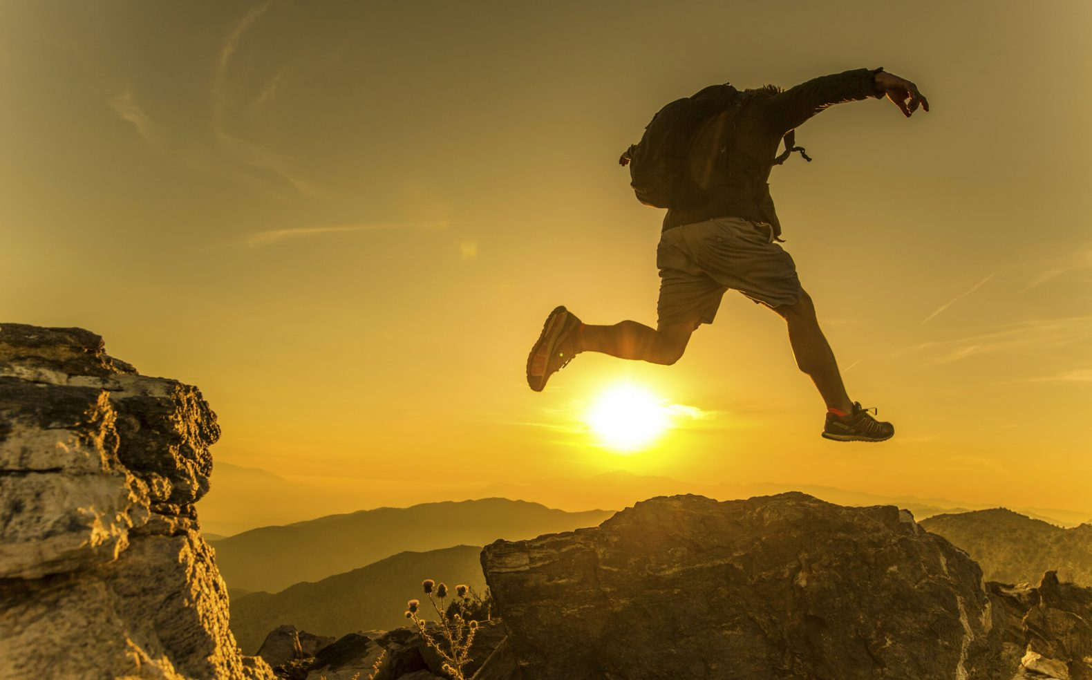A young man in hiking gear wearing a backpack taking a jump between boulders while climbing in the mountains during sunset.