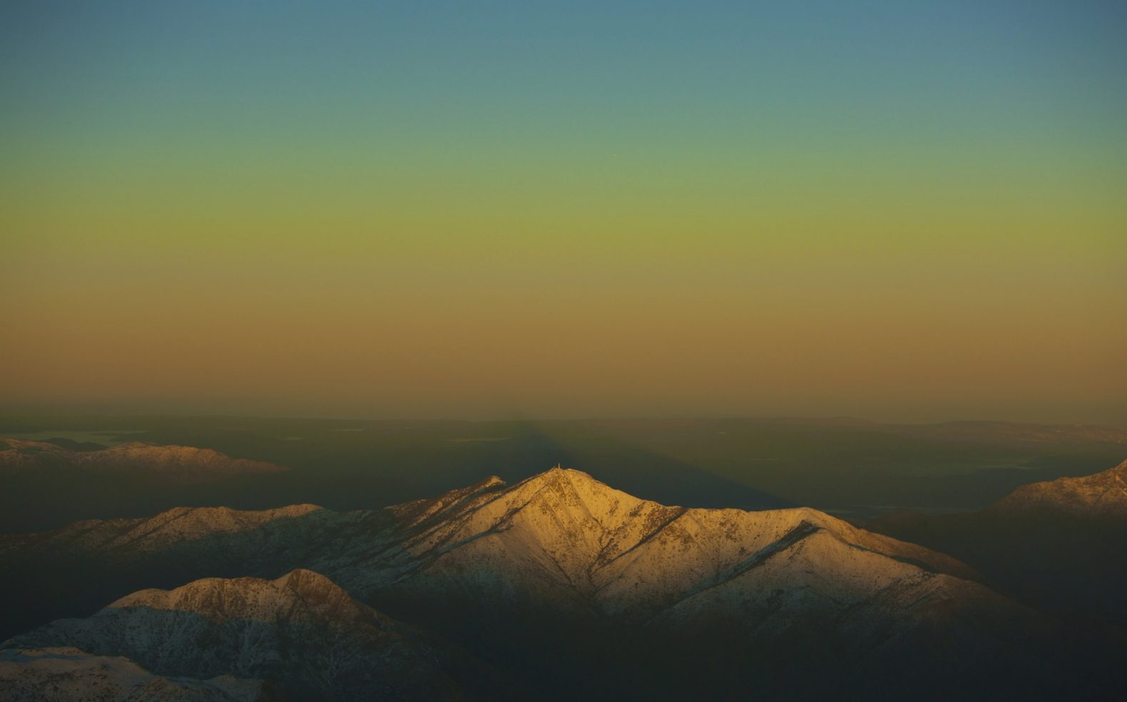 An aerial view of an alpine mountain landscape during dusk through a sky of subtle blue and orange hues.