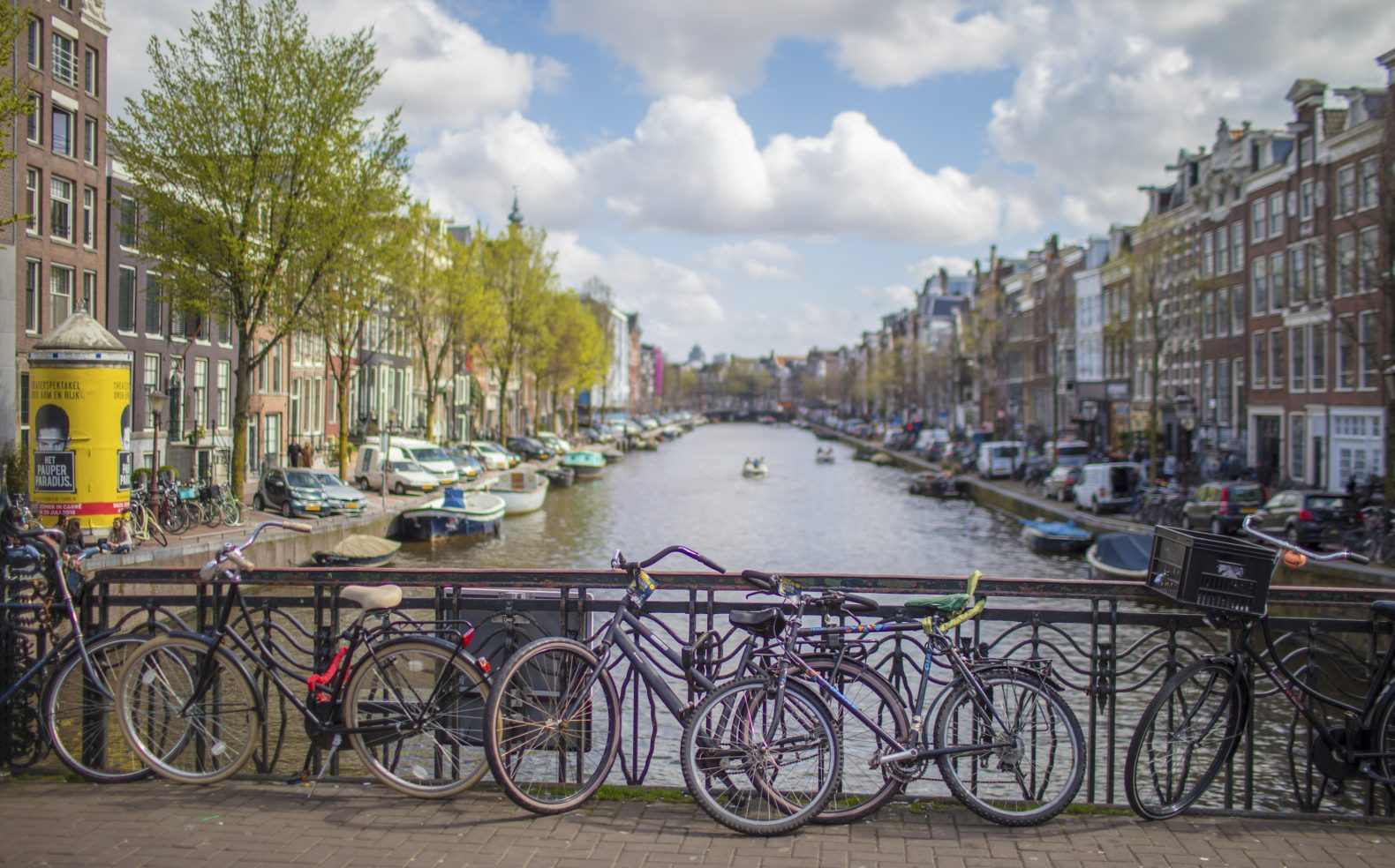 Professional travel photograph of bikes leaning against a metal bridge railing overlooking a canal in Amsterdam.