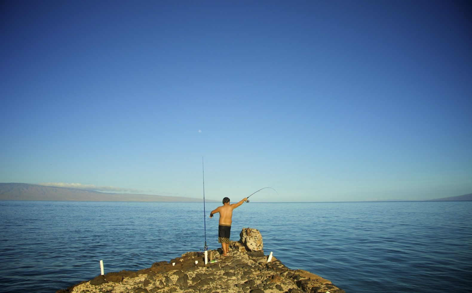 Professional travel photograph of a boy fishing from a rock surrounded by an expansive water view and distant mountains.