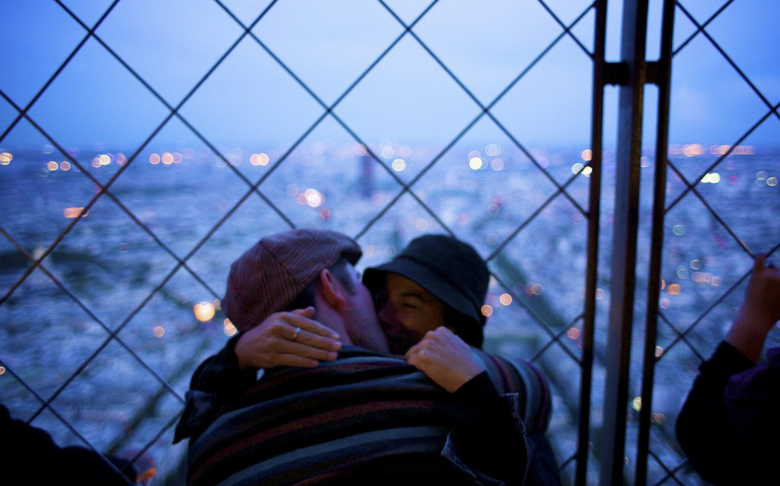 Professional travel photograph of a couple kissing against a fence overlooking a city at dusk.