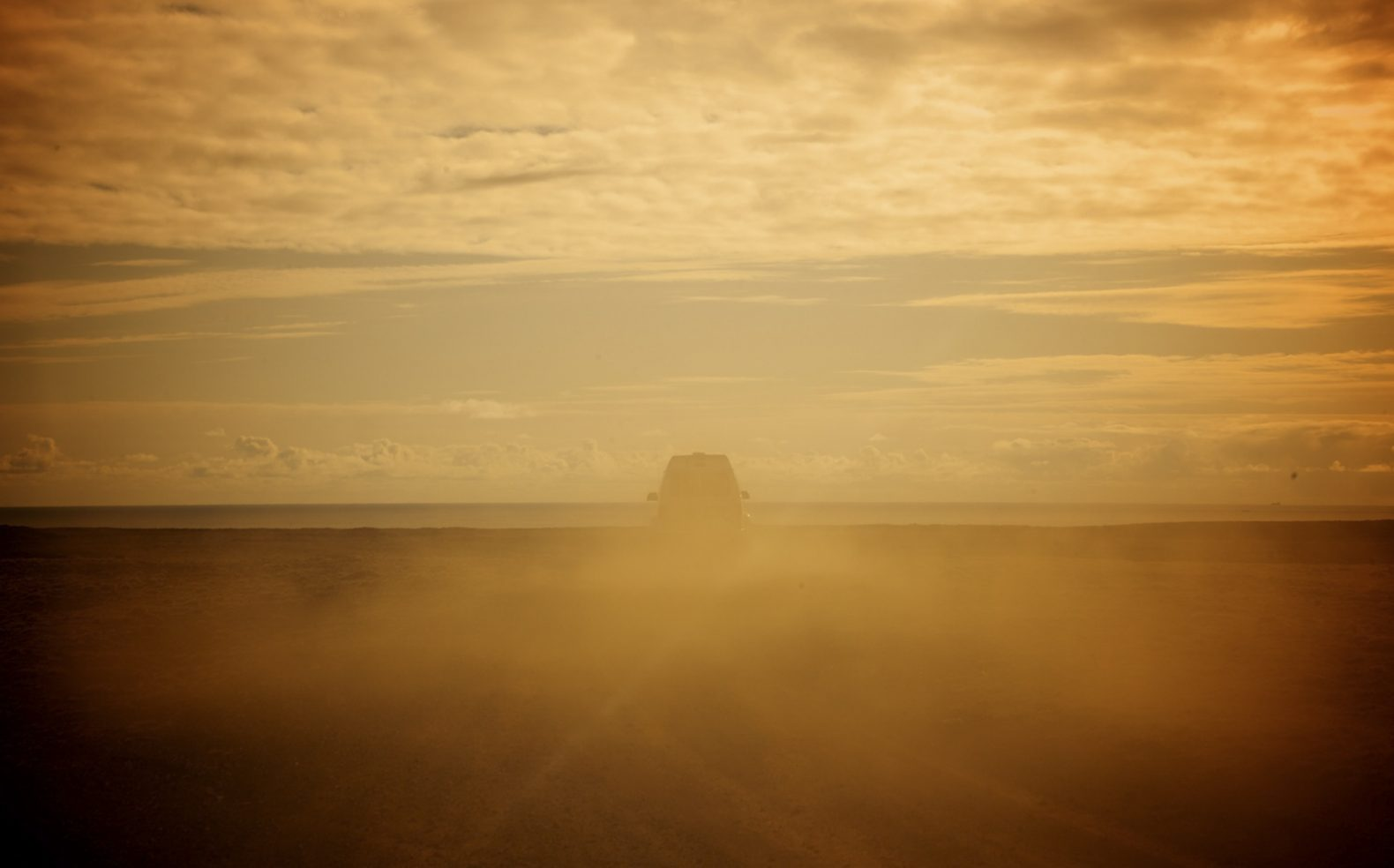 Professional travel photograph of a van obscured through swirling dirt while driving away on a dusty dirt road.