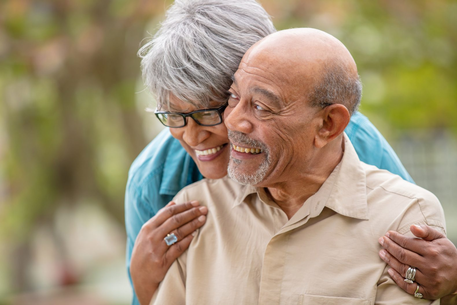 Professional production photograph of an older couple embracing with green foliage in the background