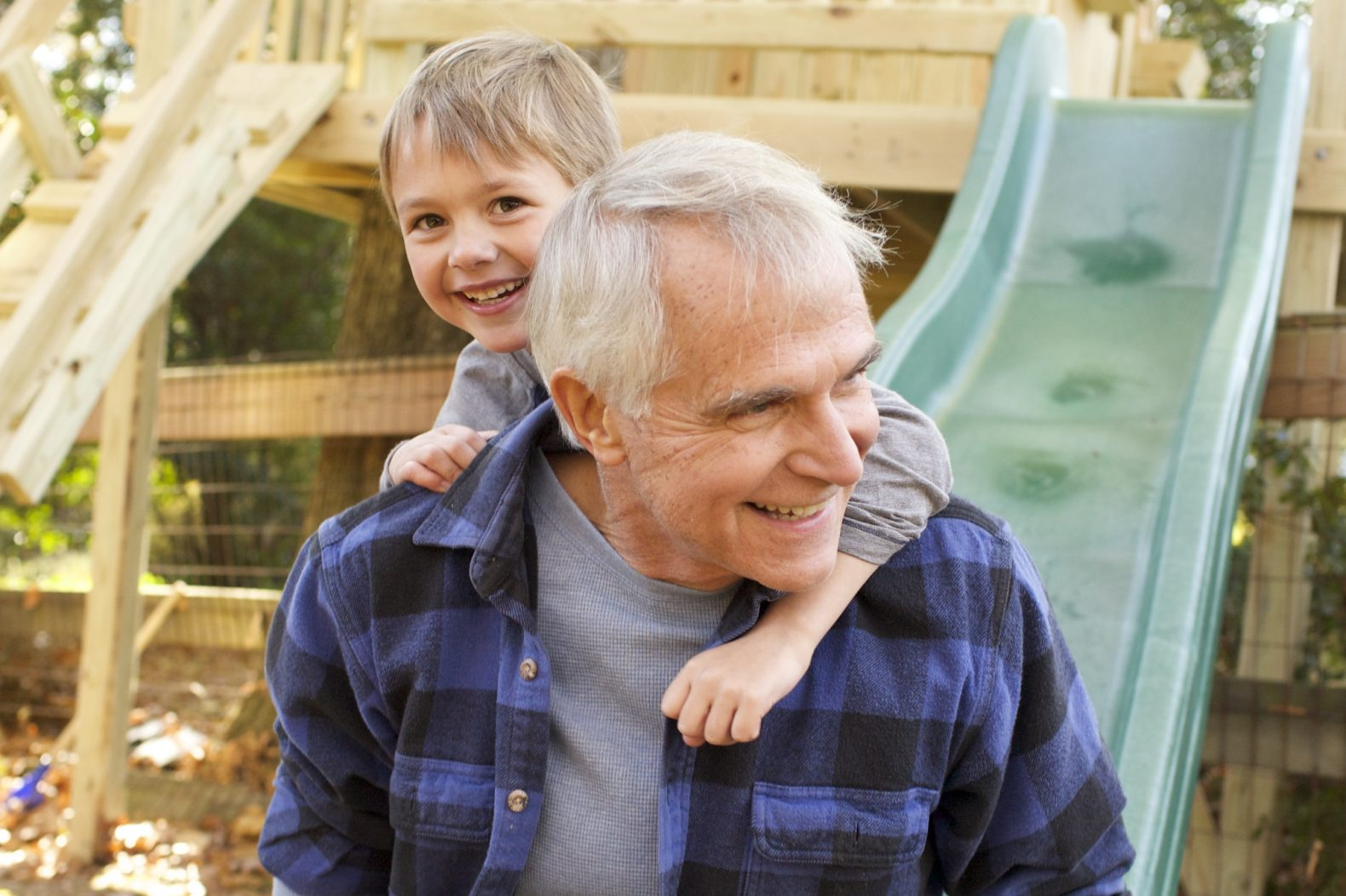 A grandpa in fall attire with his toddler grandson on his back in front of a swingset