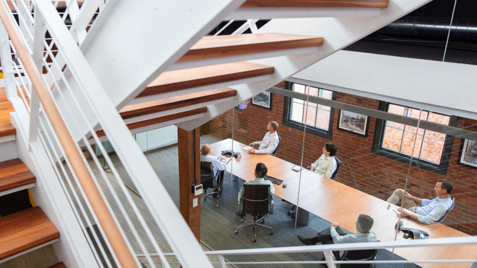employees sitting at a conference room table seen through staircase above